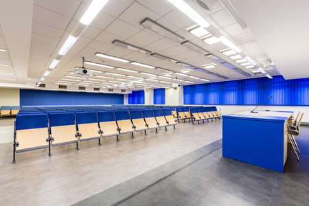 Light, spacious auditorium with blue details, wood chairs and desk