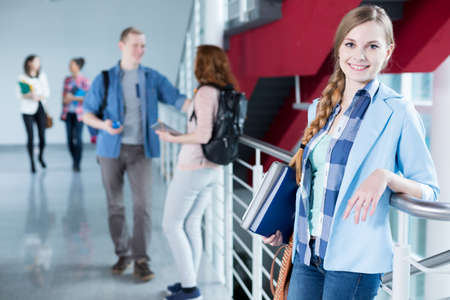 secondary education: Happy, attractive student at university, standing against railing