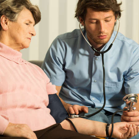 blood pressure gauge: Young handsome doctor using blood pressure gauge Stock Photo