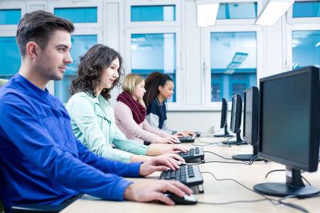 estudiantes universitarios: Disparo de los estudiantes que usan computadoras durante una clase de tecnología de la información