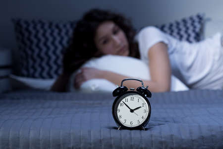 sad lady: Shot of an alarm clock put on a bed and a young girl laying in the background Stock Photo