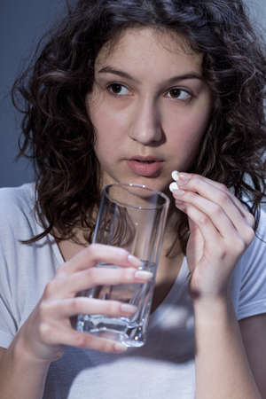 abuser: Shot of a young girl taking a pill