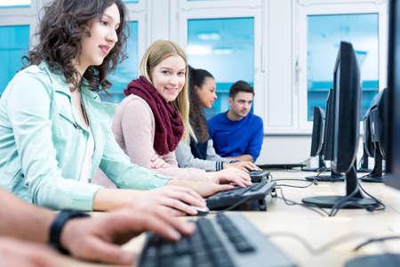 tecnologias de la informacion: Disparo de un estudiante sonriente y sus compañeros de trabajo en una sala de ordenadores