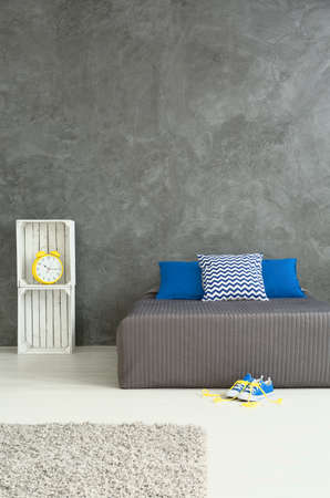 idea comfortable: Shot of a grey bedroom decorated with blue and yellow accessories