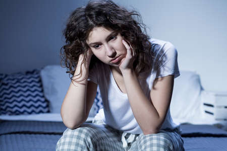 woman in bed: Shot of a sad young woman sitting on her bed Stock Photo