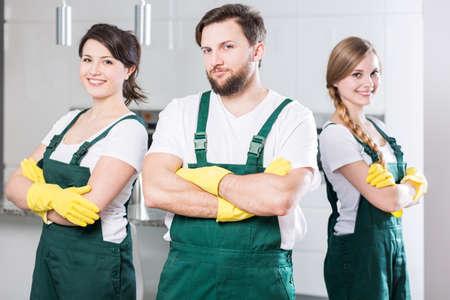 hombres trabajando: Tres jóvenes con uniformes de limpieza que se unen