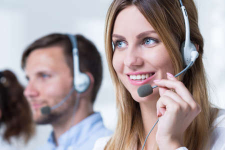 telemarketer: Young female telemarketer with headphones and work in corporation