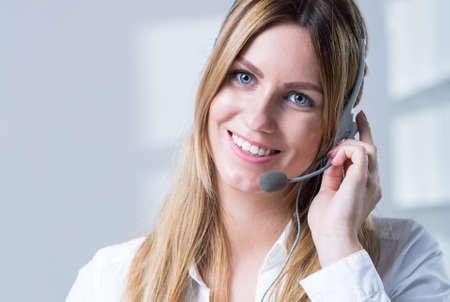 Wijfje telemarketer met hoofdtelefoons het verzorgen van de klant