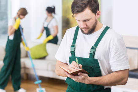 Busy young boss of cleaning company writing down the notes Stock Photo
