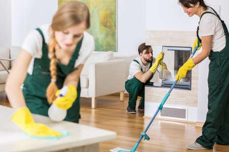 hombres trabajando: Tres jóvenes profesionales de la limpieza de los uniformes de limpieza amplia sala de estar Foto de archivo