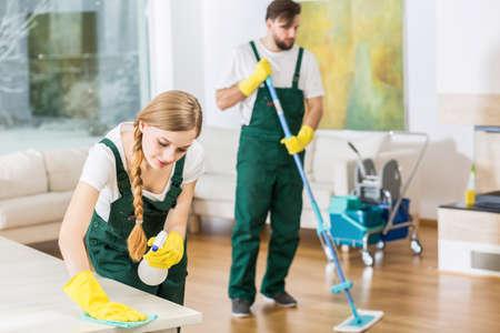 젊은 전문 청소사 정확한 넓은 아파트 청소. 테이블을 연마하는 바닥과 소녀를 걸러내는 남자 스톡 콘텐츠