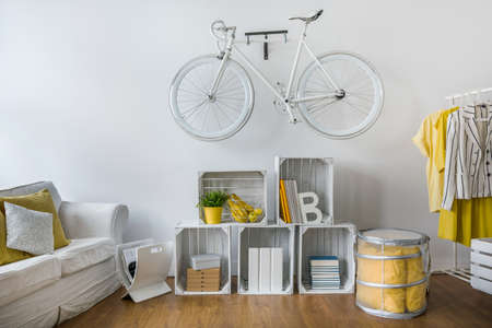 original: Modern stylish lounge with shelf of wooden boxes. White vintage bicycle hanging on wall