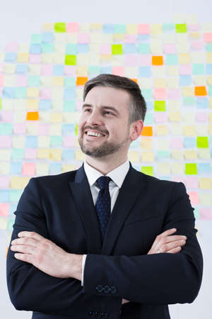 sticky hands: Handsome young creative businessman standing with crossed hands. Behind him wall full of sticky notes