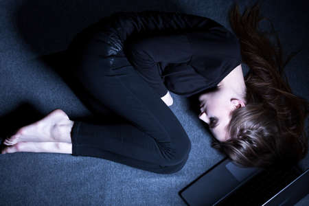 Young teenage girl with depression lying alone on floor in dark room Stock Photo