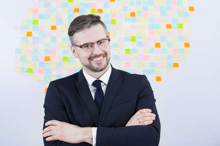 sticky hands: Smiling young handsome businessman with crossed hands on background of sticky notes