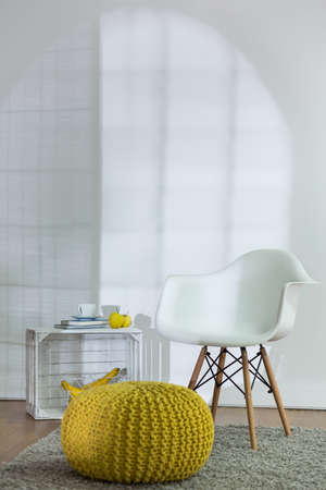 pouf: New modern design of living room with white armchair and yellow pouf