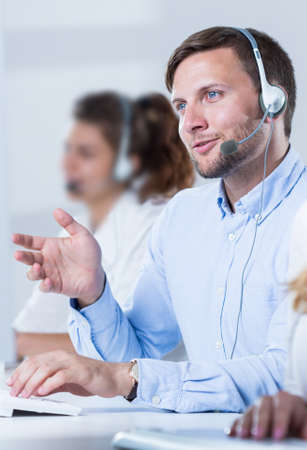 color consultant: Young handsome man taking with client on headphones