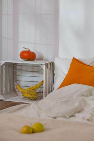 interior decor: Close-up of apples and pumpkin in modern simple bedroom. Mattress on wooden floor as a bed