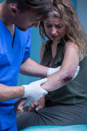 medicate: Injured woman with bloody elbow wound and young surgeon in white medical gloves.