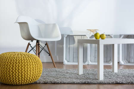 pouf: Yellow pouf, white armchair and coffee table in modern designed loft