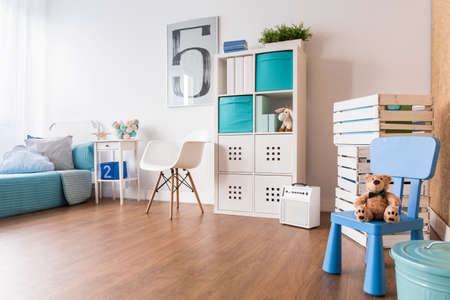 Spacious room with wooden floor with big space for playing with toys. Modern designed interior for boy Banco de Imagens