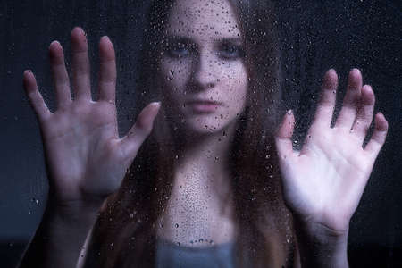 cry for help: Young girl with mental problem behind glass with raindrops. Two hands leaning on glass