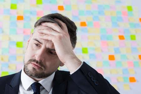 duties: Businessman with headache tired of large number of duties in company Stock Photo
