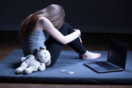 depressed teen: Broken down lonely teenage girl with depression sitting alone in room