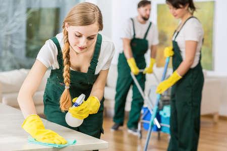 Jonge mooie schoonmaak meisje in uniform het polijsten van de marmeren tafel Stockfoto