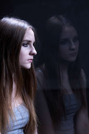 tough girl: Depressed young girl addicted to tough drugs. Sitting alone in dark room