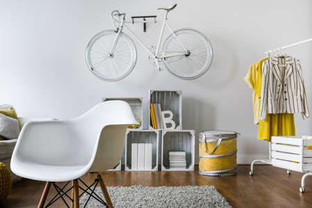 original bike: Small hipsters room with original design and old fashioned bicycle on wall Stock Photo