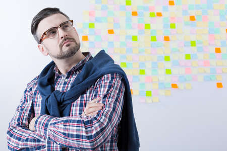 man ass: Focused middle aged man ass a leader of business company. Behind him wall with sticky notes Stock Photo