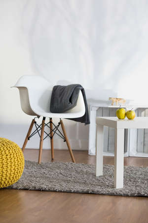 color design: Rest corner in modern lounge with white armchair and coffee table