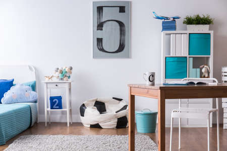 Stylish boy's room with wooden desk and pillow in football ball shape