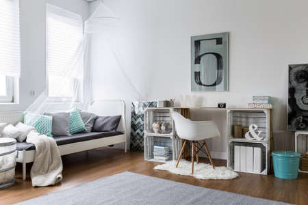 Cozy hipster bedroom with wooden floor and original desk. White bed with color pillows and canopy