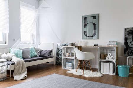 case moderne: camera da letto pantaloni a vita bassa accogliente con pavimento in legno e scrivania originale. letto bianco con cuscini di colore e baldacchino