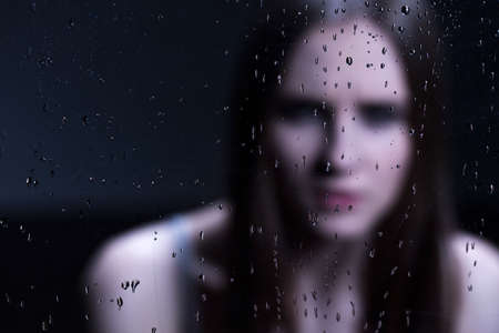 raindrops: Young depressed girl behind glass with drops