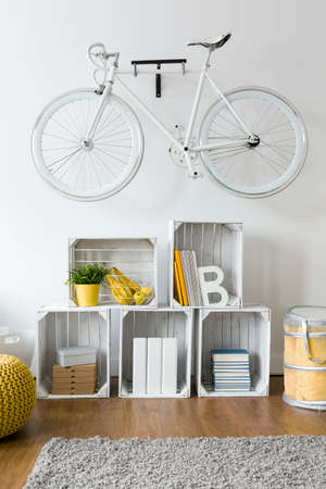 original bike: Trendy up-to-date design of spacious living room. Shelf made of wooden boxes and vintage bicycle above them Stock Photo