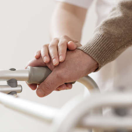 Physiotherapist supporting disabled man