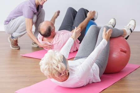 persona de la tercera edad: Mayor que ejercita en bola de gimnasio con instructor profesional.