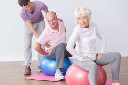 salud y deporte: Mayores que ejercitan en bolas de la gimnasia con el instructor profesional.