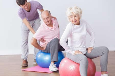 Senioren auf Gymnastikbälle mit professionellen Instruktor trainieren.