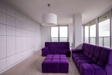 hassock: Fashionable violet lounge suite in minimalist apartment Stock Photo