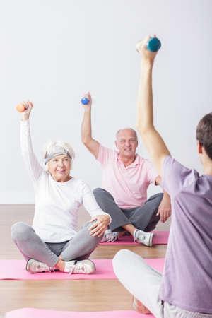 salud y deporte: Las personas mayores durante los ejercicios con el instructor de fitness profesional. Foto de archivo