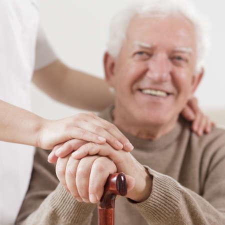 Älterer Mann und hilfsbereite Krankenschwester