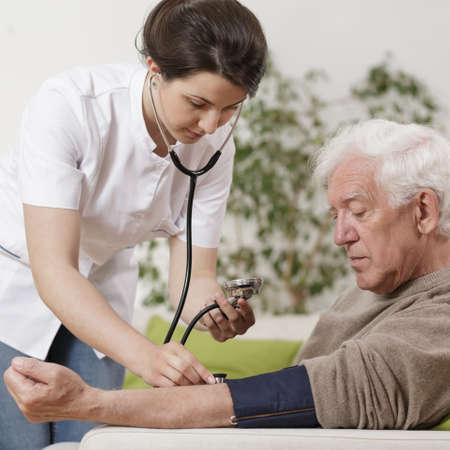 health care facility: Young nurse taking blood pressure