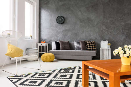 Grey living room with sofa, chair, small wood table yellow details and pattern decorations Zdjęcie Seryjne