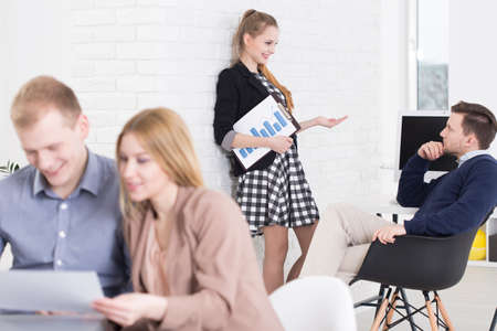 youth group: Businesspeople working together in light, modern office, woman holding graph Stock Photo