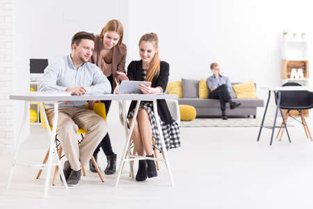 beside table: Creative businesspeople sitting beside table, working in light, modern office