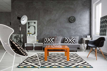 Trendy, grey living room with sofa, chairs, standing lamp, wood coffee-table and pattern decorations in black and white